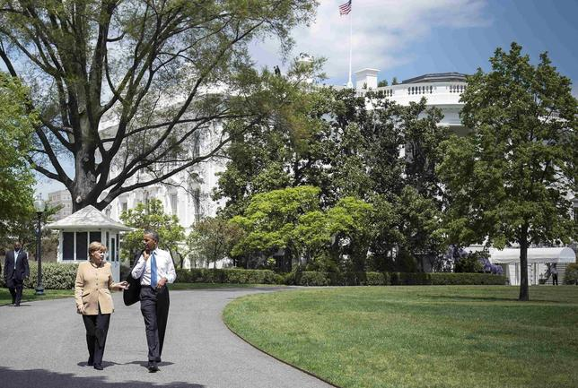 U.S. President Barack Obama (R) and German Chancellor Angela Merkel walk following their meeting to the herb and vegetable garden of the White House in Washington May 2, 2014. REUTERS/Guido Bergmann/Bundesregierung/Handout
