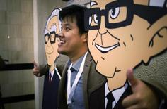 A Berkshire Hathaway shareholder poses with caricatures of CEO Warren Buffett (L) and Vice-Chairman Charlie Munger at a welcome cocktail reception in Omaha, Nebraska May 2, 2014, in the lead up to the Berkshire Hathaway annual meeting on May 3, 2014. REUTERS/Rick Wilking
