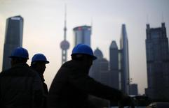 Construction workers stand on a street corner at the financial district of Pudong in Shanghai March 11, 2014. REUTERS/Carlos Barria