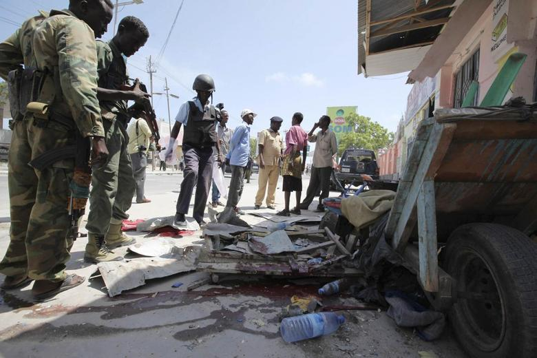 Somali soldiers stand at the scene of an explosion in the capital Mogadishu May 3, 2014. At least three people were killed and several wounded in Mogadishu on Saturday when a bomb exploded on a busy street in the Somali capital, a police official and witnesses said. REUTERS/Omar Faruk
