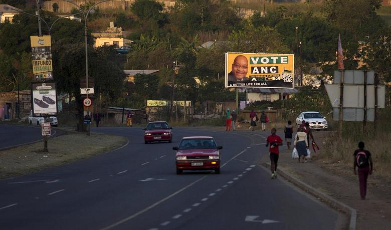 Residents wait for taxi transport beneath election posters in Pietermaritzburg in South Africa's KwaZulu Nataal province, in this picture taken April 29, 2014. REUTERS/Rogan Ward
