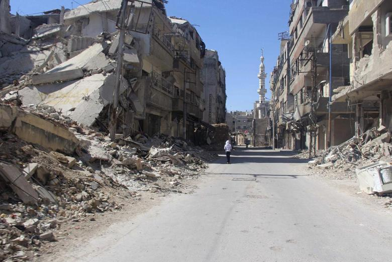 A resident walks past damaged buildings in the Damascus suburb of Zamalka May 2, 2014. Picture taken May 2, 2014. REUTERS/Badra Mamet