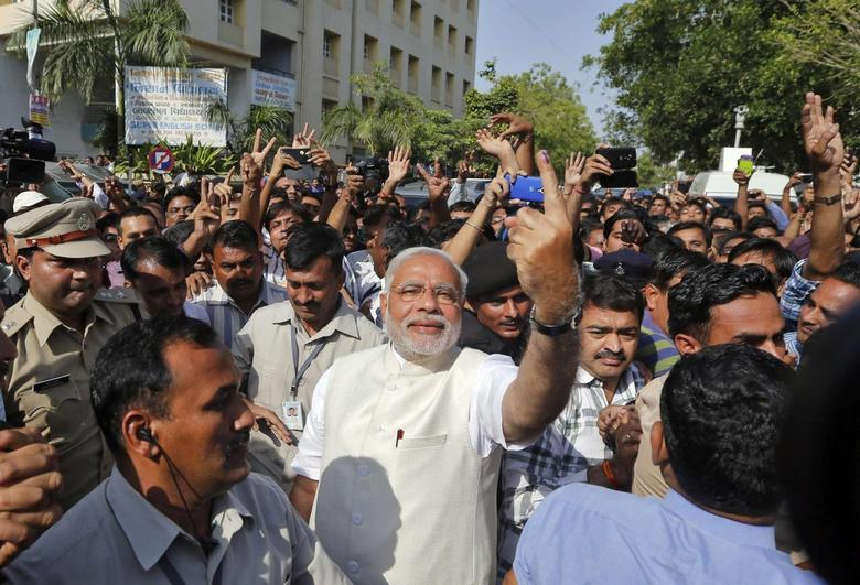 Hindu nationalist Narendra Modi (C), the prime ministerial candidate for India's main opposition Bharatiya Janata Party (BJP), shows his ink-marked finger to his supporters after casting his vote at a polling station during the seventh phase of India's general election in the western Indian city of Ahmedabad April 30, 2014. REUTERS/Amit Dave