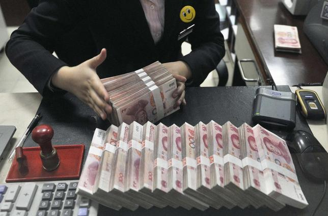 A clerk arranges bundles of 100 Chinese yuan banknotes at a branch of China Merchants Bank in Hefei, Anhui province March 17, 2014. REUTERS/Stringer