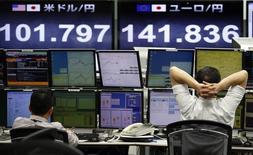 Работники трейдинговой конторы сидят перед экранами, отображающими курс иены к доллару США и евро, 18 марта 2014 года. Иена достигла максимума двух недель против доллара в понедельник, поскольку аппетит к риску был подавлен данными о сокращении активности в промсекторе Китая четвертый месяц подряд. REUTERS/Toru Hanai