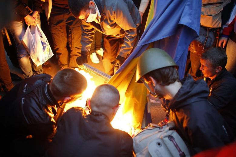 Pro-Russia protesters burn a Ukranian flag outside the district council building in Donetsk, eastern Ukraine May 4, 2014. REUTERS/Marko Djurica
