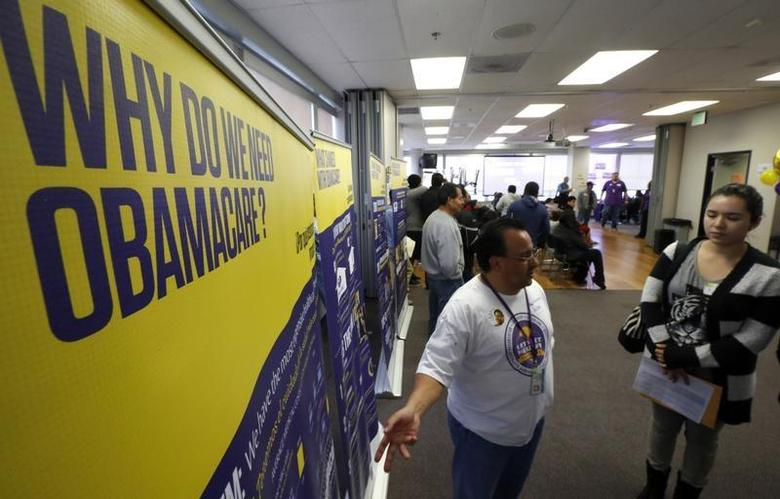 Julian Gomez (L) explains Obamacare to people at a health insurance enrolment event in Commerce, California March 31, 2014. REUTERS/Lucy Nicholson