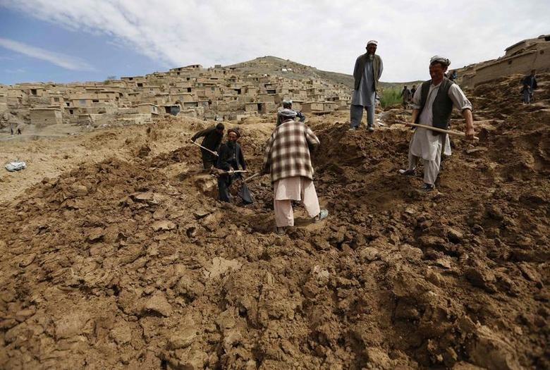 Afghan villagers excavate for dead bodies at the site of a landslide that occured on Friday at the Argo district in Badakhshan province May 5, 2014. REUTERS/Mohammad Ismail
