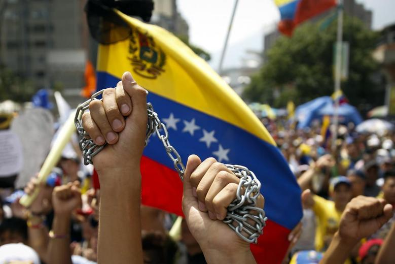 Anti-government protesters hold up chains during a May Day demonstration in Caracas May 1, 2014. REUTERS/Carlos Garcia Rawlins