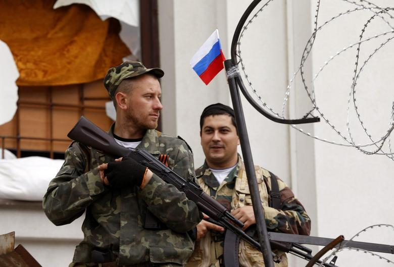 Armed pro-Russian activists stand guard at the entrance of the seized regional government headquarters in Luhansk, eastern Ukraine, May 5, 2014. REUTERS/Vasily Fedosenko