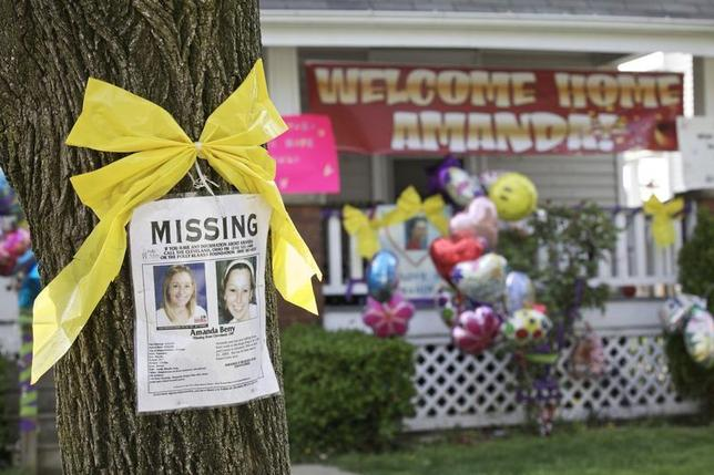 A missing person poster for Amanda Berry, one of the three woman found alive after vanishing for about a decade in their own neighborhood, is pictured on a tree in front of the home of Berry's sister Beth, which is adorned with balloons and a welcome home banner for Amanda, in Cleveland, Ohio May 7, 2013. REUTERS/John Gress