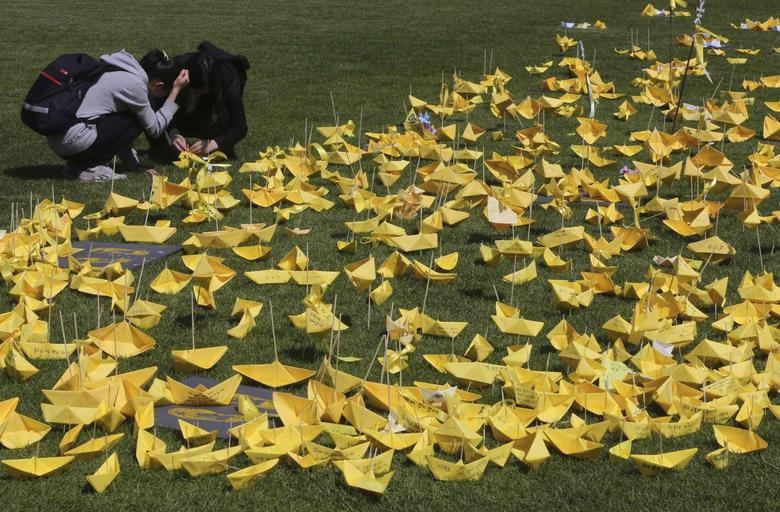 Mourners place yellow coloured paper ships dedicated to missing and dead passengers of the sunken passenger ship Sewol near a memorial altar for victims set up at Seoul City Hall Plaza May 5, 2014. REUTERS/Park Dong-ju/Yonhap