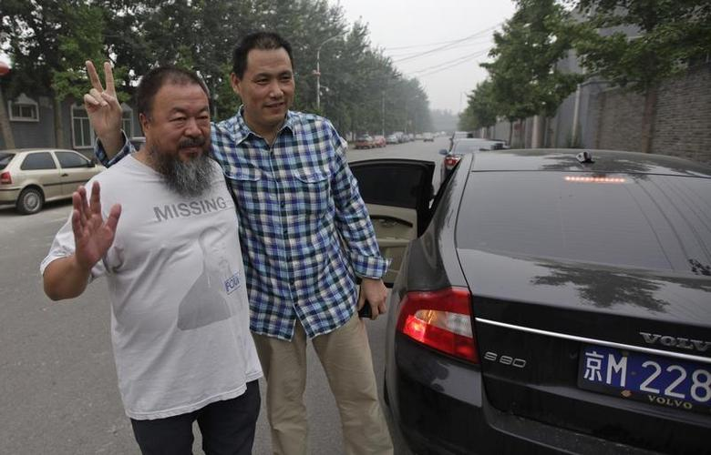 Chinese dissident artist Ai Weiwei (L) poses outside his studio for a photograph with his lawyer Pu Zhiqiang as the latter leaves for the courthouse before a court hearing in Beijing, July 20, 2012. REUTERS/Petar Kujundzic