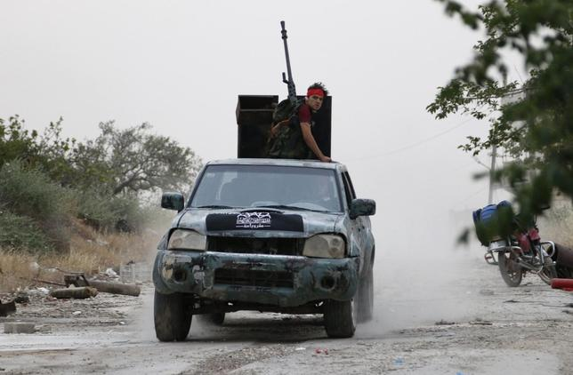 A rebel fighter from the Islamic Front sits on a pick-up truck mounted with an anti-aircraft weapon in Maarat Al-Nouman, Idlib province May 5, 2014. REUTERS/Rasem Ghareeb