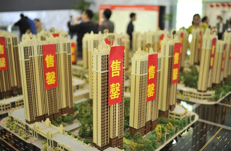 Customers visit a real estate exhibition displaying models of apartments in Hefei, Anhui province, May 1, 2014. REUTERS/Stringer