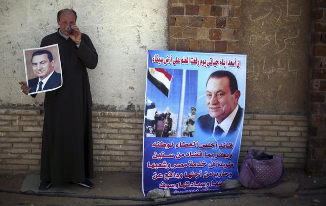 Reda Shehata, a supporter of Egypt's former president Hosni Mubarak drinks tea as he holds his poster, outside the police academy, where Mubarak's trial will take place, in Cairo April 7, 2014. Banner (R) reads,   REUTERS/Amr Abdallah Dalsh