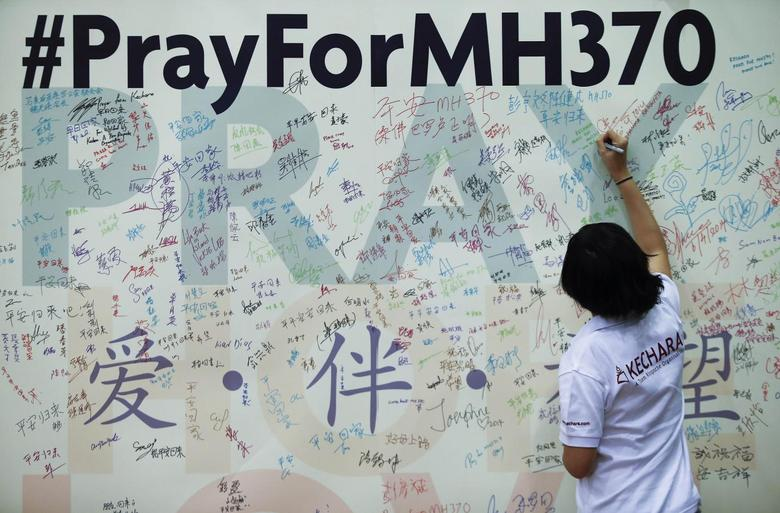 A woman writes a message on a board for family members of passengers onboard the missing Malaysia Airlines Flight MH370 at the Malaysian Chinese Association (MCA) headquarters in Kuala Lumpur April 6, 2014. REUTERS/Samsul Said