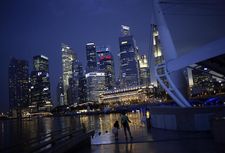 People take photos with the skyline of the financial district of Singapore in the background April 14, 2014. REUTERS/Edgar Su