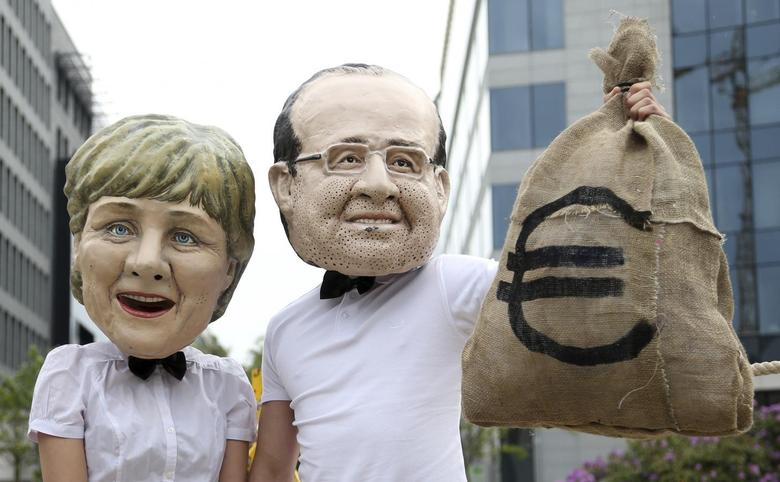 Activists wearing masks depicting German Chancellor Angela Merkel (L) and French President Francois Hollande stage a protest outside a meeting of European finance ministers in Brussels May 6, 2014. REUTERS/Francois Lenoir
