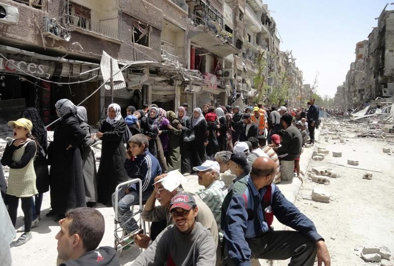 Residents queue as they wait to receive food aid distributed by the UNRWA at the Palestinian refugee camp of Yarmouk, south of Damascus, May 4, 2014. REUTERS/Rame Alsayed