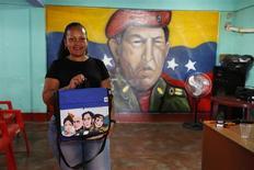 Aura Aguilera, de 34 años, quien trabaja a tiempo completo en el desarrollo comunitario, frente a un mural de Hugo Chávez, nov 26, 2013. El barrio de El Chaparral comenzó a recibir financiamiento del Gobierno de Venezuela en el 2005, cortesía de un plan de Hugo Chávez para combatir la pobreza transfiriendo miles de millones de dólares de los ingresos petroleros a las comunidades del país. REUTERS/Carlos García Rawlins