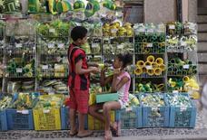 Crianças que vendem balas nas rua brincam com cornetes em frente a loja com produtos verde-amarelos no Saara, no Rio de Janeiro. 22/04/2014 REUTERS/Ricardo Moraes
