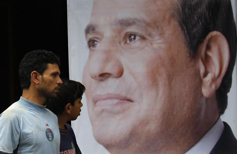 People walk past a poster of presidential candidate and former army chief Abdel Fattah al-Sisi at one of his campaign headquarters in central Cairo April 16, 2014. REUTERS/Amr Abdallah Dalsh