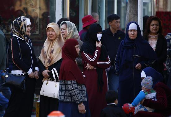 Uighur women stand next to a street to wait for a bus in downtown Urumqi, Xinjiang Uighur Autonomous Region May 1, 2014. REUTERS-Petar Kujundzic