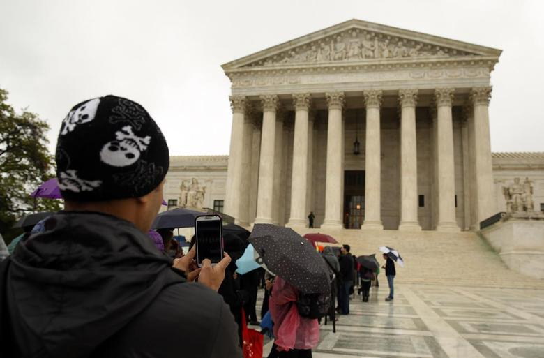 A man takes a picture with his mobile device outside of the U.S. Supreme Court in Washington April 29, 2014. REUTERS/Gary Cameron