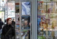 Женщина у киоска с прессой в Москве 26 ноября 2008 года. Деловая активность в секторе услуг РФ в апреле 2014 года снизилась до минимума 59 месяцев на фоне сокращения объемов производства и новых заказов, а также увольнений сотрудников, свидетельствуют результаты исследования, проведенного компанией Markit по заказу HSBC. REUTERS/Denis Sinyakov