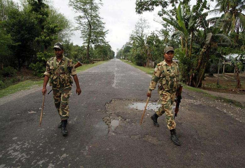 Security personnel patrol a deserted road during a curfew in Baksa district in the northeastern Indian state of Assam May 4, 2014. REUTERS/Utpal Baruah