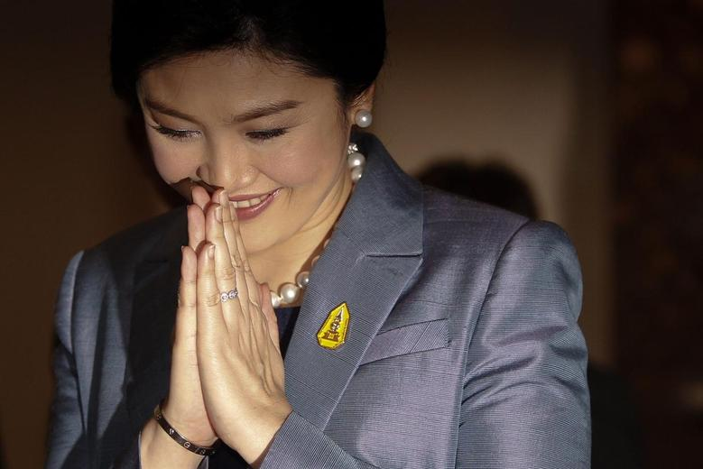Thailand's Prime Minister Yingluck Shinawatra gives a traditional greeting as she arrives at the Constitutional Court in Bangkok May 6, 2014. REUTERS/Chaiwat Subprasom