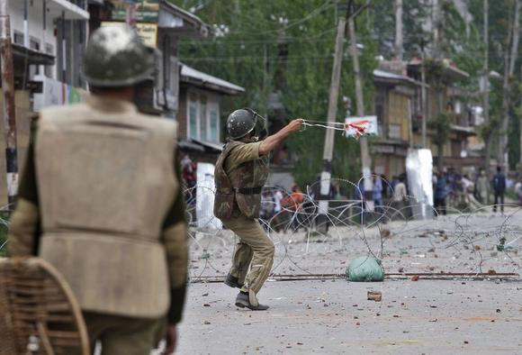 A policeman throws a stone towards Kashmiri protesters during an anti-election protest in Baramulla district, north of Srinagar May 7, 2014. REUTERS/Danish Ismail
