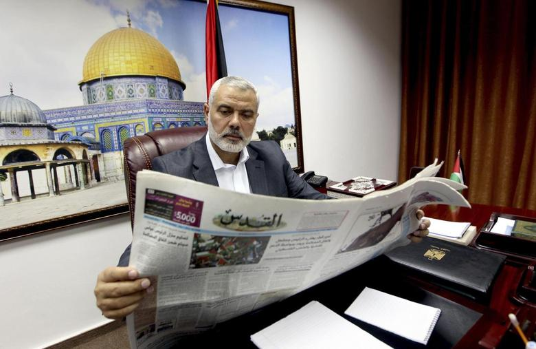 Head of the Hamas government Ismail Haniyeh reads a copy of Al-Quds newspaper at his office in Gaza City in this May 7, 2014 handout picture. REUTERS/Mohammed Al-Ostaz/Gaza Prime Minister Office (PMO)/Handout via Reuters