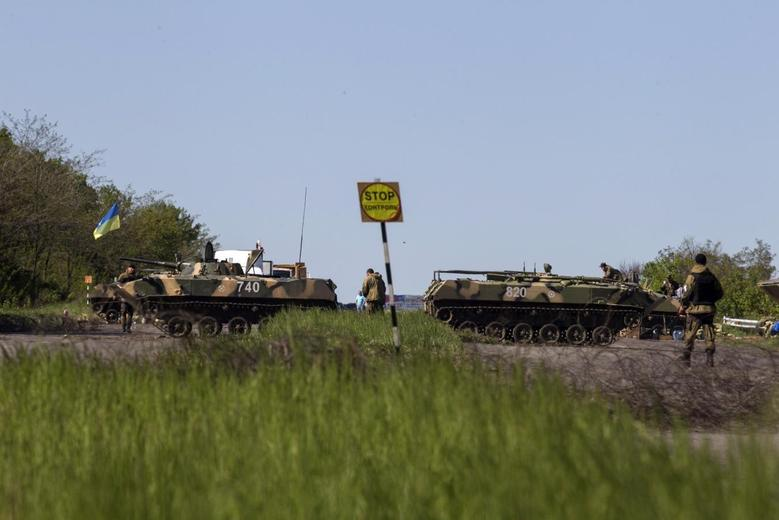 Ukrainian soldiers walk near armoured personnel carriers at a checkpoint in near the town of Slaviansk, in eastern Ukraine May 7, 2014. REUTERS/Baz Ratner
