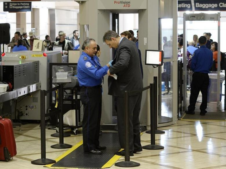 An airline passenger is patted down by a Transportation Security Administration (TSA) agent after passing through a full-body scanner at Los Angeles International Airport in Los Angeles, California February 20, 2014. REUTERS/Kevork Djansezian