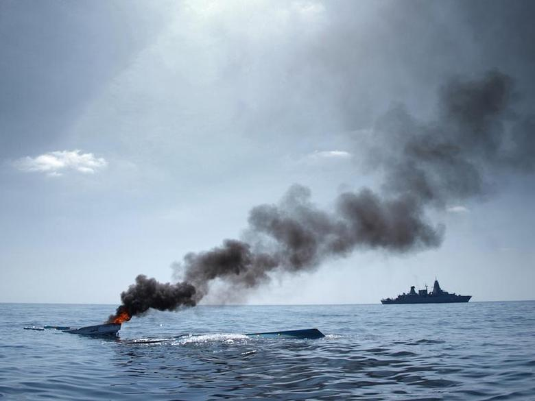 The German Frigate 'Hamburg' (R) patrols after destroying two fishing boats (L) which were discovered floating keel side up in open waters off the coast of Somalia, in this undated handout photo made available to Reuters August 15, 2011. REUTERS/Bundeswehr/Christian Laudan/Handout