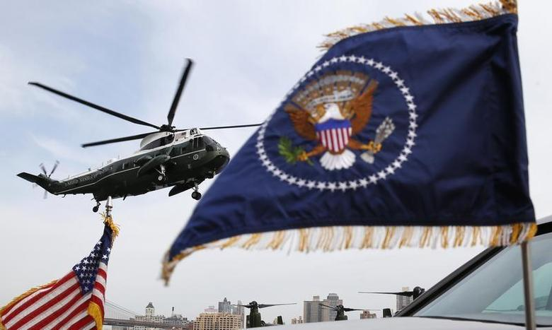 Marine One, seen through flags on the presidential limo, lands carrying U.S. President Barack Obama and first lady Michelle Obama at the Wall Street heliport in New York City April 11, 2014. REUTERS/Kevin Lamarque