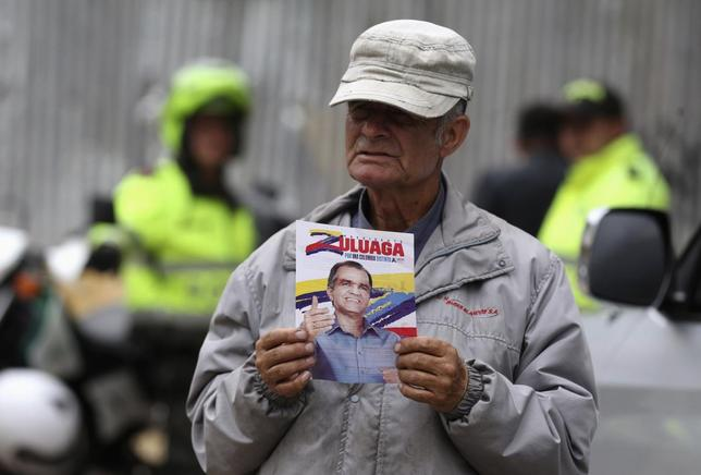 A supporter holds a leaflet while waiting for Colombian presidential candidate Oscar Ivan Zuluaga's campaign rally in the Bogota neighborhood of Suba May 6, 2014. Colombia will hold elections on May 25. REUTERS/John Vizcaino