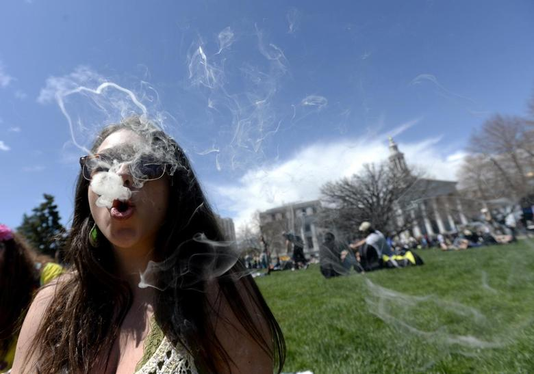 A woman blows smoke rings with marijuana smoke during the 4/20 Rally at the Civic Center in Denver, Colorado, April 20, 2014. REUTERS/Mark Leffingwell