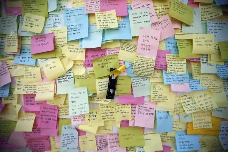 A yellow ribbon dedicated to missing and dead passengers of sunken passenger ship Sewol is seen among messages written for the victims outside the official memorial altar in Ansan May 2, 2014. REUTERS/Kim Hong-Ji