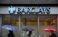 Pedestrians shelter under umbrellas as they walk past a Barclays branch in central London May 8, 2014. REUTERS/Stefan Wermuth