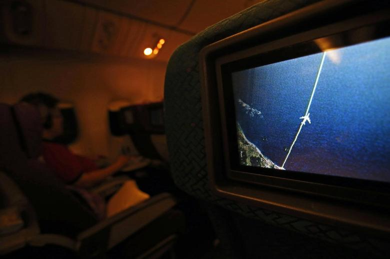 A screen on board Malaysia Airlines Boeing 777-200ER flight MH318 shows the plane's flight path as it cruises over the South China Sea from Kuala Lumpur towards Beijing, at approximately the same point when on March 8 flight MH370 lost contact with air traffic controllers, at approximately 1.30am March 17, 2014. REUTERS/Edgar Su