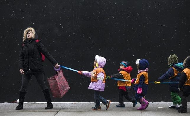A schoolteacher, attempts to catch snowflakes while leading her students to a library from school in the Harlem neighborhood, located in the Manhattan borough of New York on January 10, 2014. REUTERS/Adrees Latif