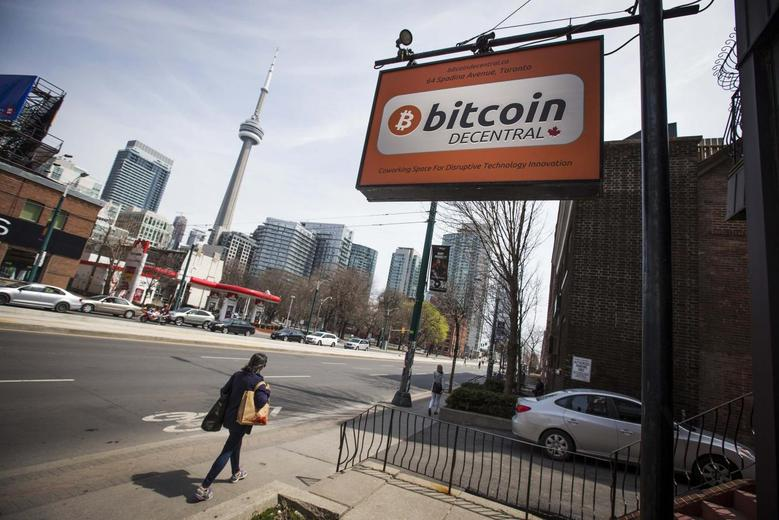 People walk by a ''Bitcoin Decentral'' sign in Toronto, May 8, 2014. REUTERS/Mark Blinch
