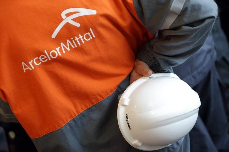 A worker holds his helmet as he listens to French President's speech during a visit at ArcelorMittal steel factory in Florange, Eastern France, September 26, 2013. REUTERS/Philippe Wojazer