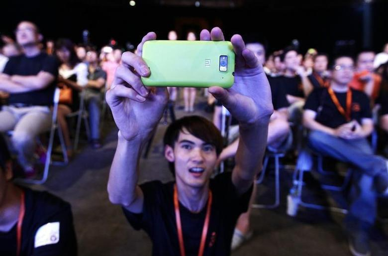 A user of Xiaomi uses his mobile phone to take a photo at a launch ceremony of Xiaomi Phone 2 in Beijing August 16, 2012. REUTERS/Jason Lee