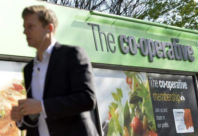 A pedestrian passes a Co-operative retail store in east London, April 10, 2014. REUTERS/Toby Melville