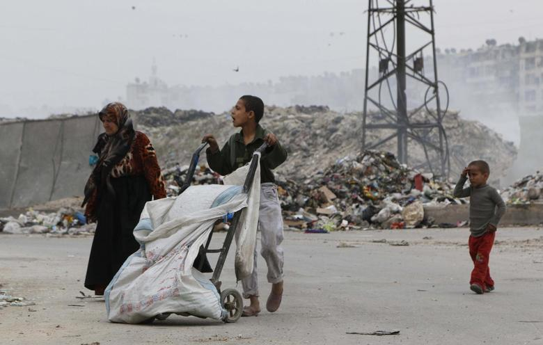 Members of a family walk along a street covered with garbage in al-Kalaseh neighborhood in Aleppo May 6, 2014. REUTERS/Hosam Katan