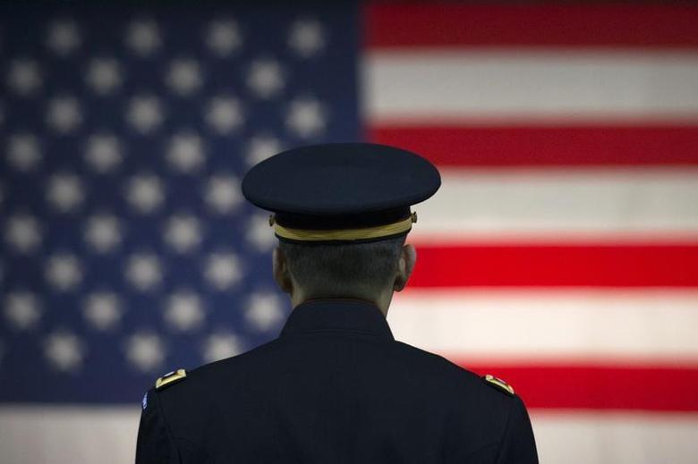 A U.S. Army officer listens to a speaker with the U.S. flag in the background at the Hiring our Heroes job fair in New York March 27, 2014. REUTERS/Brendan McDermid